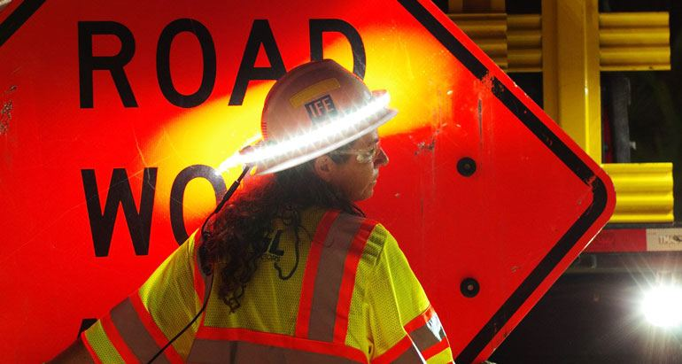 Construction worker installing a road work traffic sign